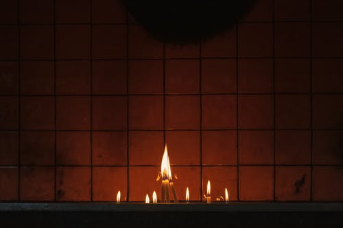 Lighted Candles on Brown Brick Wall