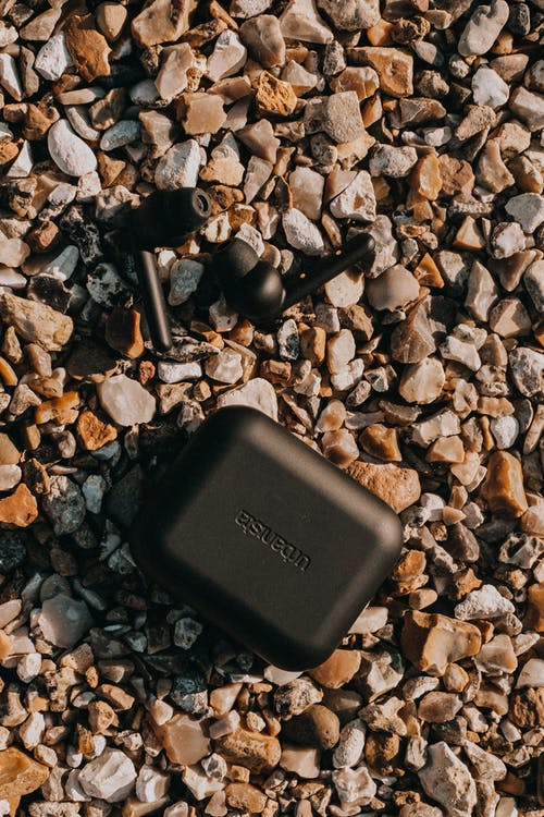 From above of black true wireless earbuds and battery case on dry rocky surface