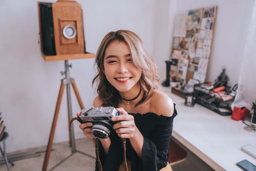 Cheerful Asian woman with photo camera