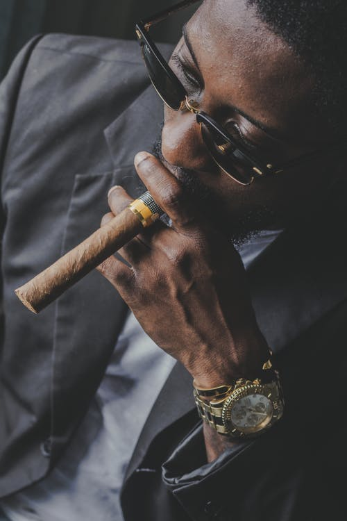 From above of crop pondering African American male entrepreneur in trendy suit and wristwatch smoking cigar while looking away