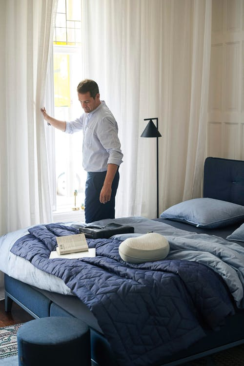 Man in White Dress Shirt Standing on Bed
