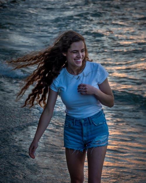 Cheerful woman walking on seaside
