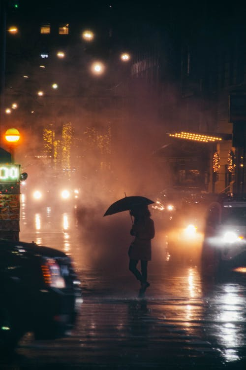Back view of faceless female pedestrian with umbrella crossing road near various vehicles with glowing headlights in rainy city at night