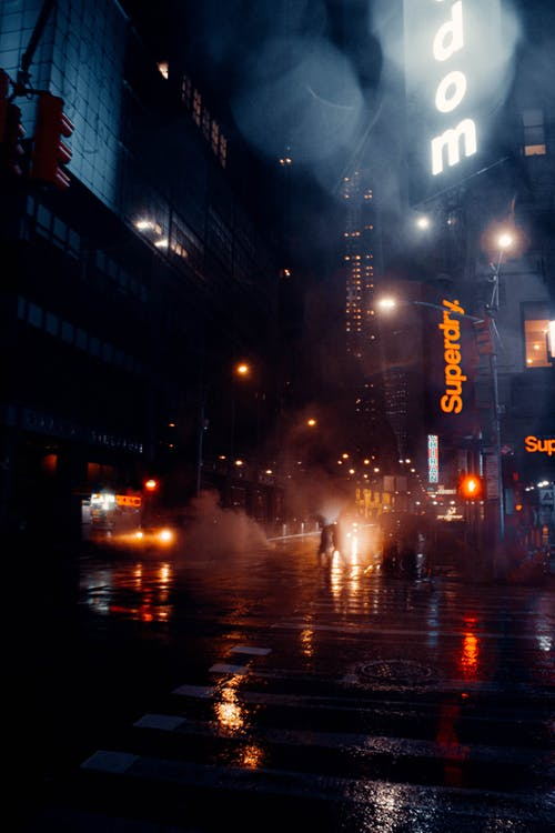 Modern skyscraper facades and wet road in night city