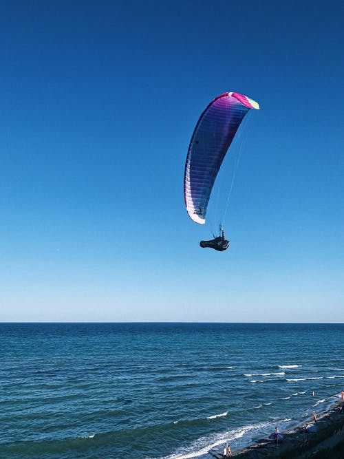 Person in Red and White Parachute Under Blue Sky