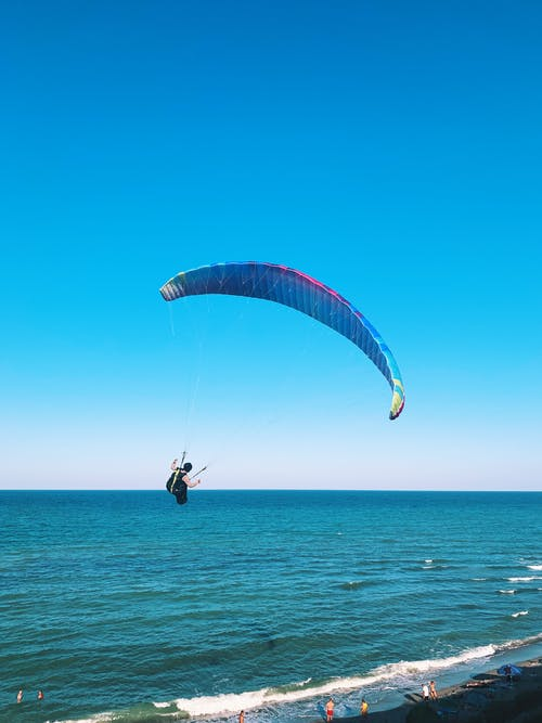 Back view of anonymous person flying on paraglider near waving ocean and beach on summer sunny day
