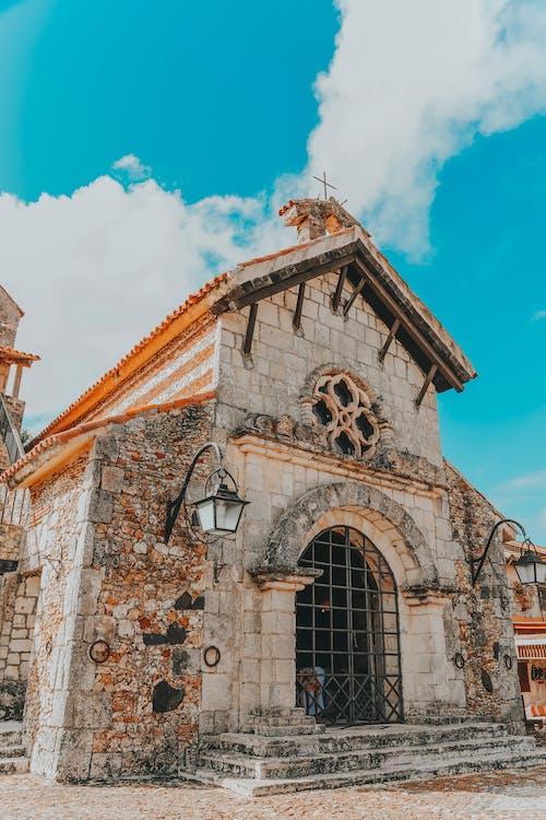 Old stone church facade under blue cloudy sky