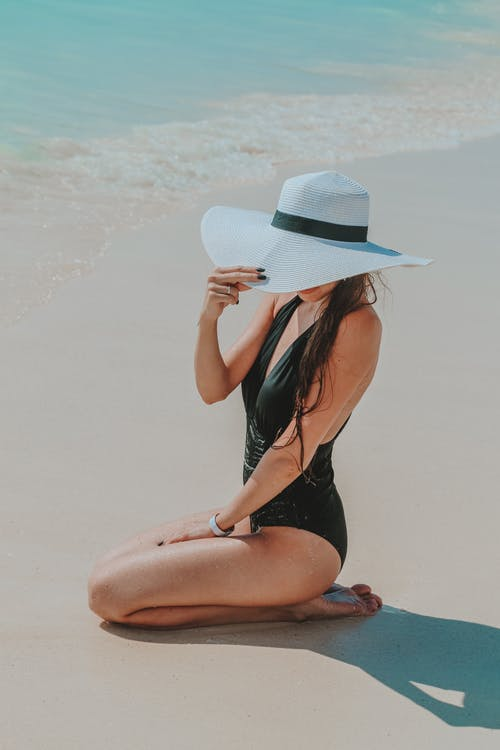 From above side view of anonymous trendy slim barefoot female tourist in black swimwear touching hat while sitting on sandy ocean beach