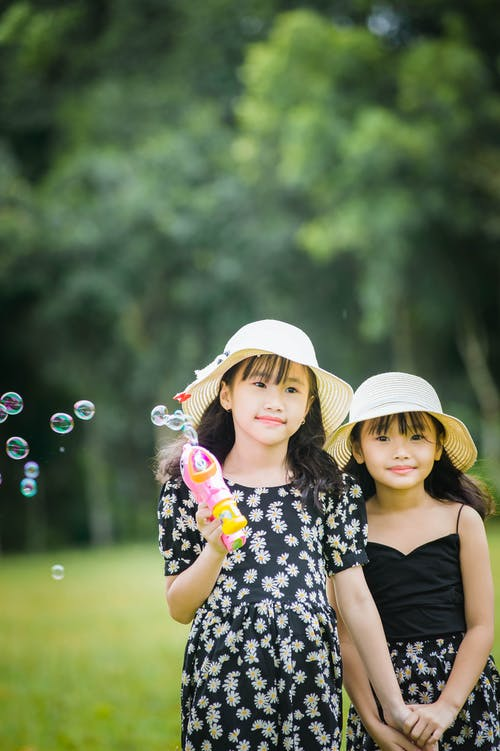 Happy female Asian kids with dark hair in straw hats blowing soap bubbles with bubble blower while standing on green lawn with trees on blurred background