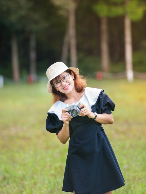 Positive Asian female photographer in eyeglasses wearing straw hat and black dress looking at camera while standing on field with photo camera in hands near trees