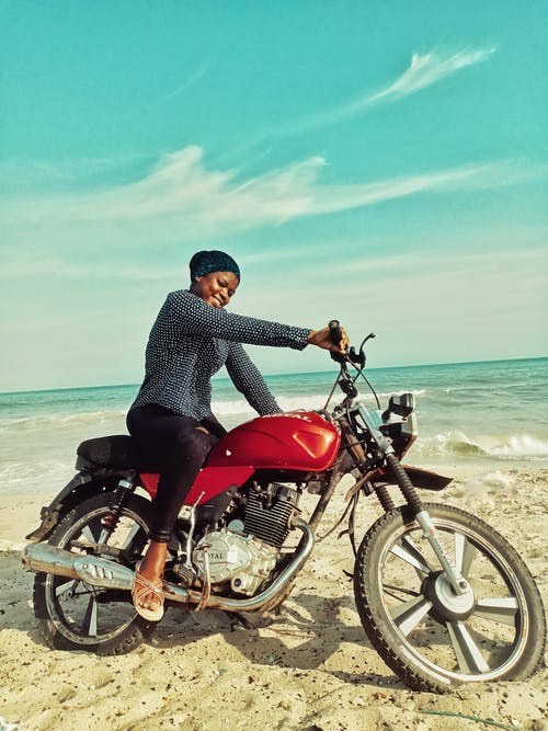 Full body of happy African American female in headscarf looking at camera while sitting on red motorcycle on sandy beach near waving sea