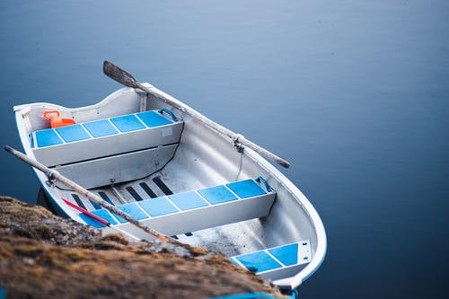 White and Blue Boat on Body of Water