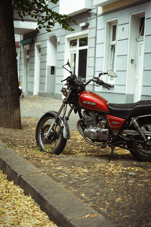 Red and Black Standard Motorcycle Parked Beside White Wooden Door