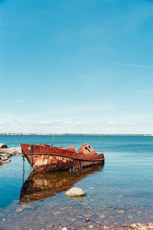 Brown Boat on Sea Under Blue Sky