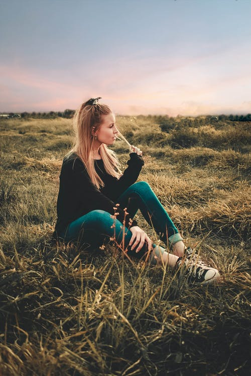 Woman in Black Long Sleeve Shirt and Blue Denim Jeans Sitting on Brown Grass Field during