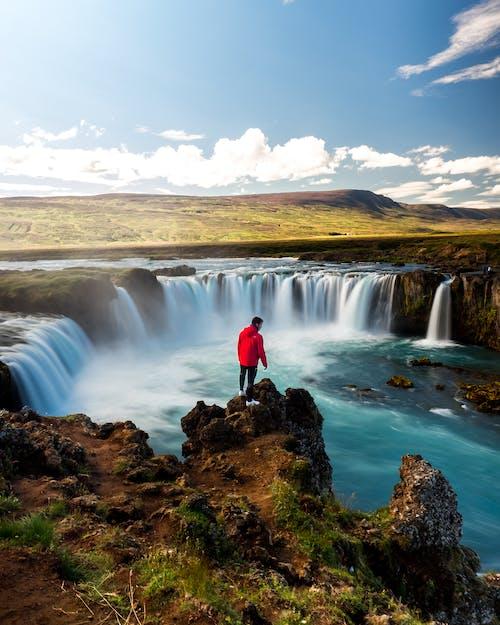 Man in Red Jacket Standing on Brown Rock Near Waterfalls