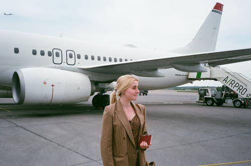 Smiling tourist with passport near airplane on road