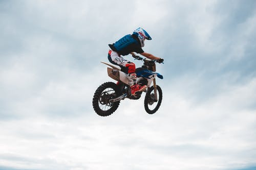 Unrecognizable man rider performing stunt in air