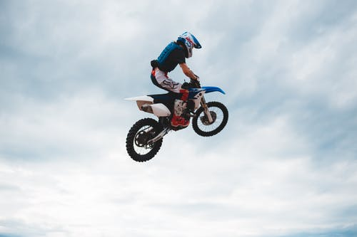 Side view of anonymous male biker in helmet on motorcycle doing trick while jumping high into air against cloudy sky in daylight