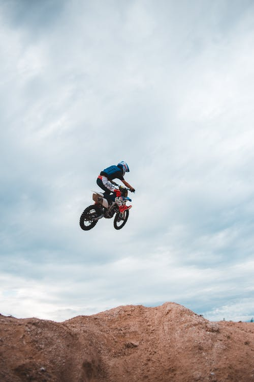 From below side view of anonymous male biker doing stunt while jumping high into air above sand hill against cloudy sky