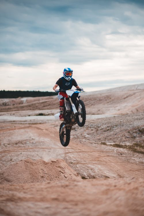 Full body of anonymous male biker riding enduro motorcycle on hill and jumping into air against cloudy sky in nature