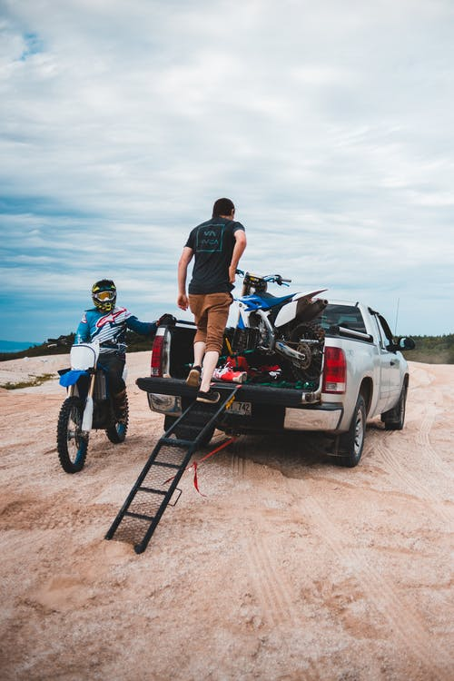 Unrecognizable male bikers loading motorbike in white pickup truck on sandy road in countryside against cloudy sky in nature outside