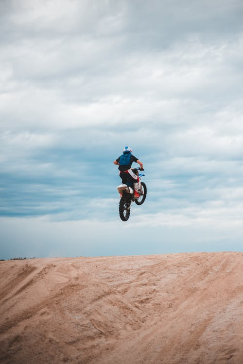 Anonymous sportsman riding enduro motorcycle in air