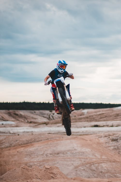 Unrecognizable male racer in helmet riding sandy road on rear wheel of motorcycle while performing stunt in nature against cloudy sky