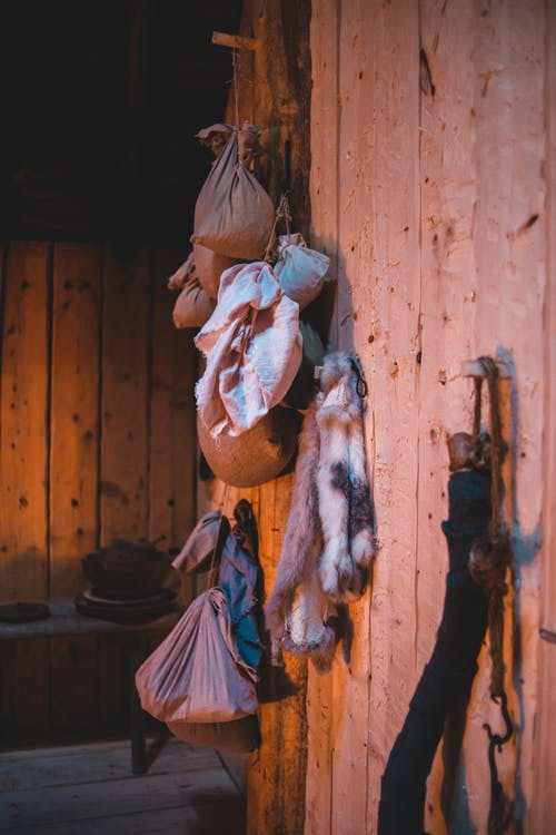 Various sacks hanging on wooden wall of small cozy house located in countryside