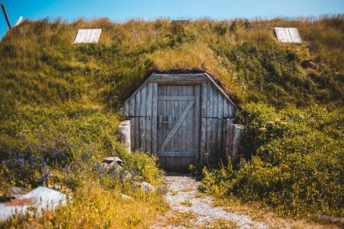 Old typical sod roofed house with wooden doors located in Norstead Viking Village in Newfoundland on sunny day