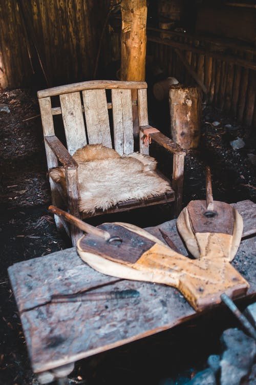 Shabby wooden chair and blacksmith board in abandoned house