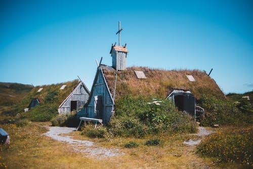 Old wooden church and house on meadow in countryside