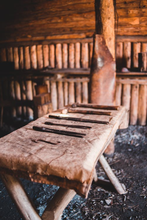 Old table with various carpentry tools placed in aged shabby wooden workshop in Norstead Viking Village in Canada