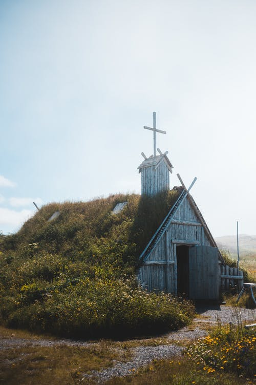 Ancient wooden church with grassy roof located on meadow in countryside in Newfoundland on sunny day