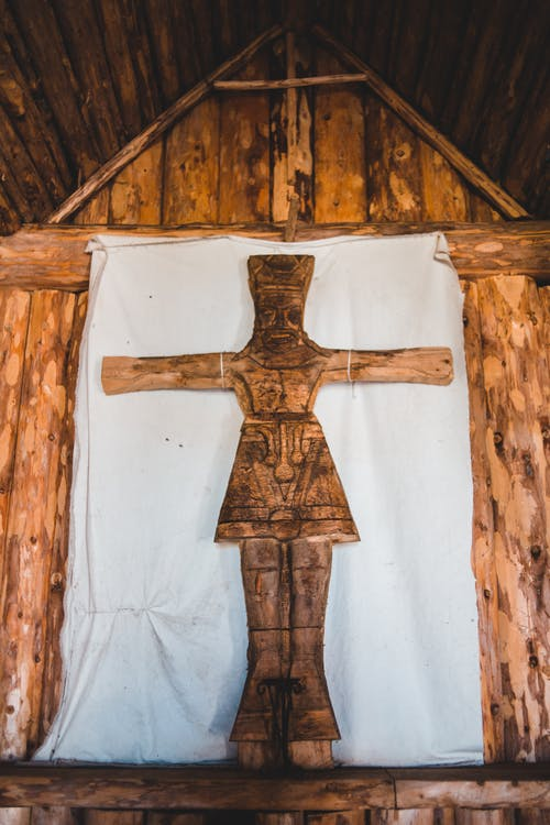 Low angle of old carved wooden cross on altar of ancient church located in Norstead Viking Village in Canada