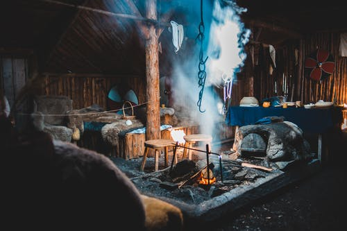 Burning bonfire inside of aged wooden house with bed and armchairs in Norstead Viking Village