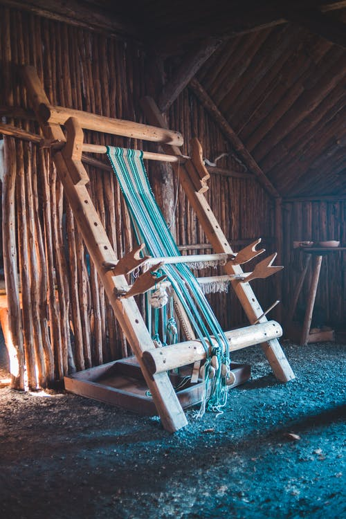 Aged wooden loom with weaved yarn
