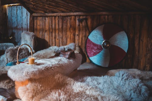 Interior of old wooden Viking house with furniture covered with natural fur in Norstead Village in Newfoundland