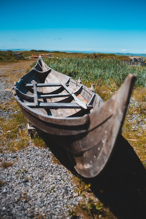 Shabby wooden boat on calm shore