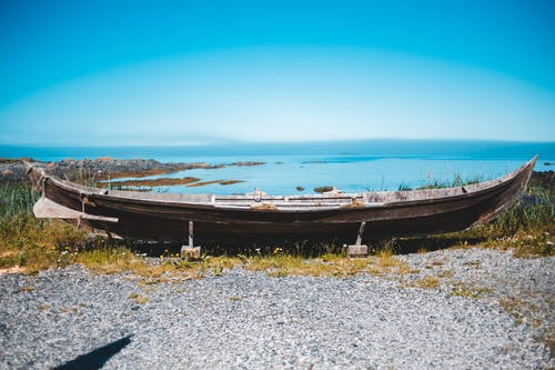 Aged boat on coast with blue ocean