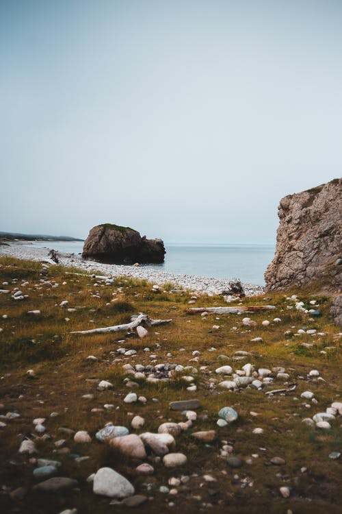 Remote peaceful coastline with cliffs in peaceful ocean water and white pebbles on green grass