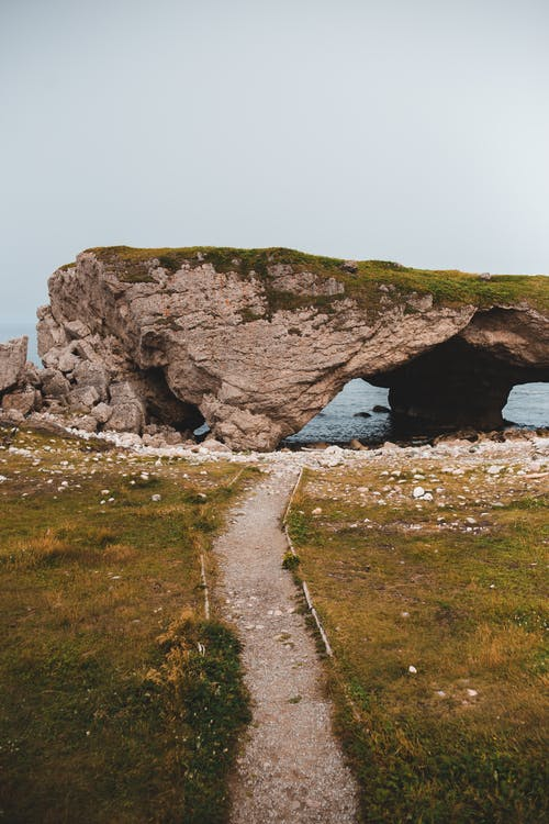 Calm shore with walkway and cliff arch