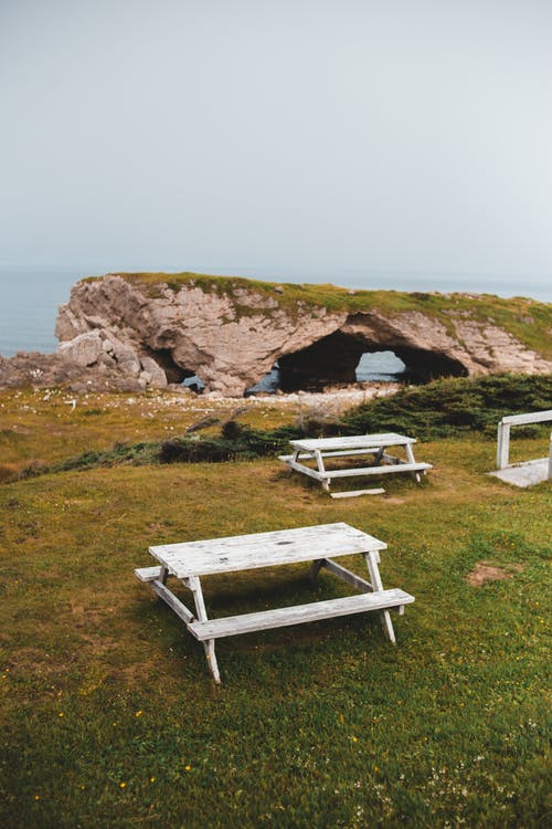 Benches on calm green shoreline with rocks