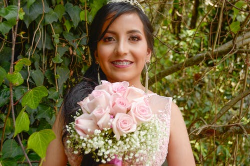 Woman in White Floral Sleeveless Dress Holding Pink Flower Bouquet