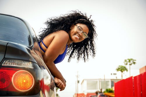 Woman in Blue Tank Top Leaning on Silver Car