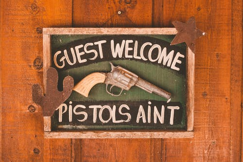 Framed rectangular signboard with inscription Guest Welcome Pistols Aint decorated with artificial gun and silhouettes of cactus and star on wooden door