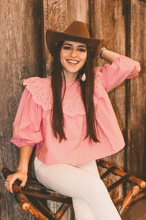 Cheerful young stylish female in pink blouse and white trousers touching hat and looking at camera with bright friendly smile