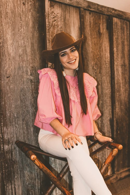 Charming young slender female in stylish pink shirt and white pants looking at camera with legs crossed and hand on knee while resting on folding chair by wooden wall