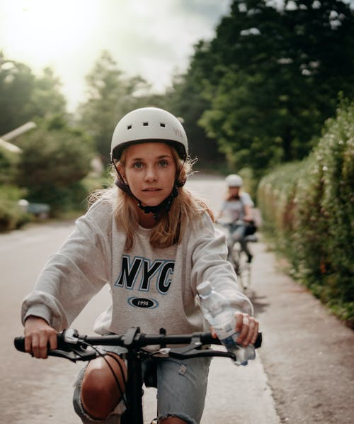 Woman in White Long Sleeve Shirt Riding Bicycle on Road