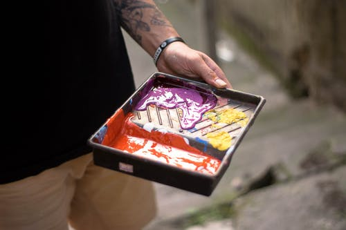 From above of crop anonymous tattooed male artist mixing colorful dye while before creating new artwork on street